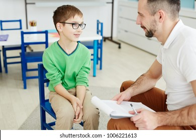 Cute schoolboy in eyeglasses answering questions of teacher at individual lesson