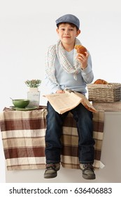 Cute schoolboy having breakfast on kitchen counter, reading newspaper acting like an adult.