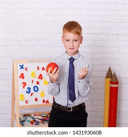 Cute schoolboy near easel is holding apple while smiling at the camera.  Childhood. Education. School. Advertisement and people concept