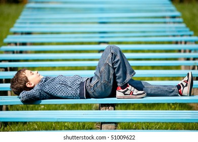 Cute schoolboy relaxing sitting on bench in a park