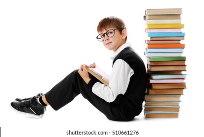 Cute schoolboy sitting beside heap of books on white background