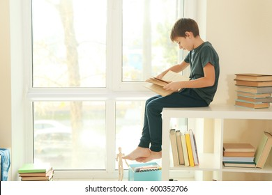 Cute schoolboy sitting beside window and reading book