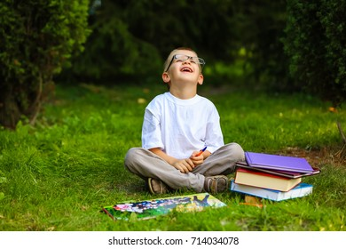 Cute schoolboy studying outdoors on bright autumn day. Boy is reading book with glasses. Back to school. Young student doing homework. Education for small kids.