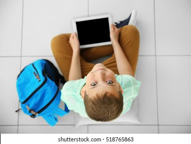 Cute schoolboy with tablet, top view