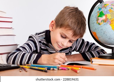 Cute schoolboy is writting isolated on a white background