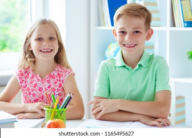 Cute schoolchildren are came back to school and learning at the table in classroom