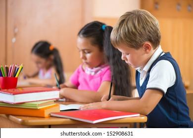 Cute schoolchildren during lesson in classroom at school