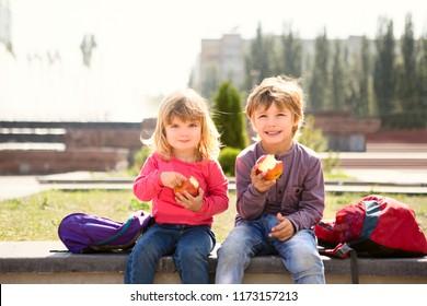Cute schoolchildren eating apples outdoors. childhood, healthy school breakfast concept.