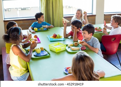 Cute schoolchildren having meal in canteen