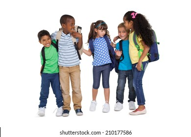 Cute schoolchildren smiling at camera and wearing backpacks on white background