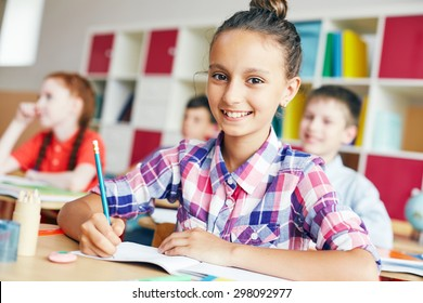 Cute schoolgirl looking at camera with smile at lesson