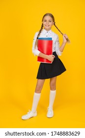 Cute schoolgirl. School education. Courses for gifted children. Basic level. Happy schoolgirl hold textbooks yellow background. Little schoolgirl back to school. Small schoolgirl wear uniform.