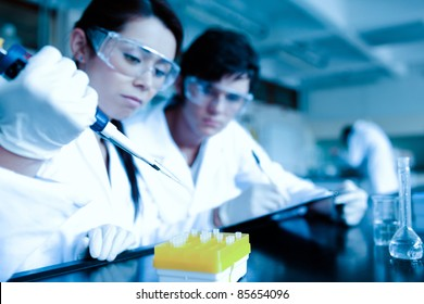 Cute scientist dropping liquid in test tubes while her partner is taking notes in a laboratory