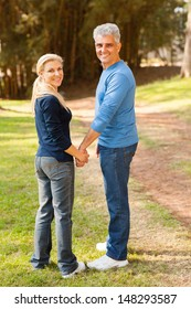 cute senior couple holding hands and looking back