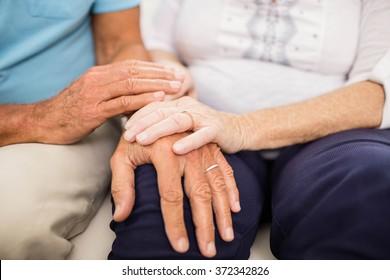 Cute senior couple holding hands on sofa