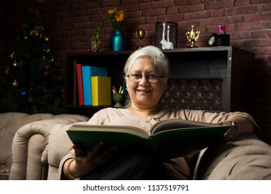 cute Senior indian/asian lady sitting on recliners chair or sofa reading book or using tab or laptop computer