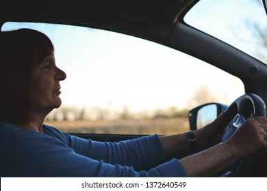 Cute senior lady happy driving car. A senior woman enjoys a newly acquired car with modern systems of active and passive safety, navigation of voice commands.