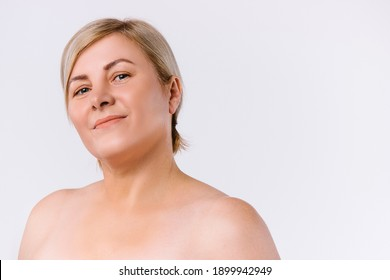 Cute senior woman with clean skin looking at the camera on a white background with side space.