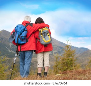 cute seniorcouple hiking in an autumn mountainlandscape. Lots of blue sky for text.