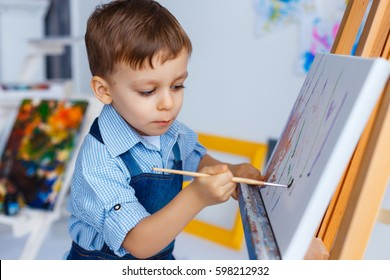 Cute, serious and focused, three years old boy in blue shirt and jeans apron drawing on canvas standing on the easel. Concept of early childhood education, painting, talent, happy family or parenting