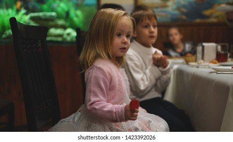 Cute serious little girl sitting at the table with her friend on the birhday party
