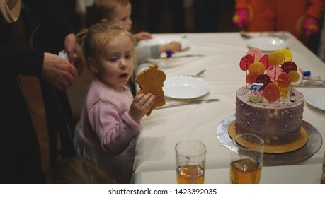 Cute serious little girl sitting at the table with her friends on the birhday party. Girl holding gingerbread