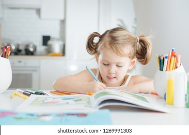 Cute serious little girl with two tails is drawing in coloring book with a blue colored pencil at home. Tip of her tounge out. Blurred background.