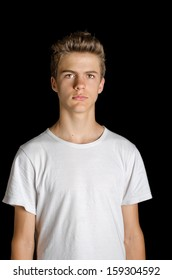 Cute serious teenage boy standing on black - isolated on black