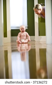 Cute seven month old chubby baby wearing diaper sitting on floor laughing at mother