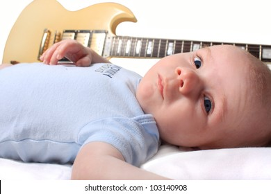 Cute seven week old newborn baby laying with a guitaron white background