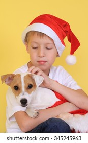 Cute seven year old boy wearing Santa hat playing with his dog Jack Russell terrier. Family, New year, Christmas time concept