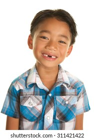 Cute Seven Year Old Filipino Boy On a white Background Smiling and Showing the gap where his two front teeth are missing,