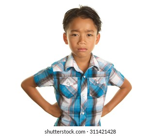 Cute Seven Year Old Filipino Boy On a white Background with his hands on his hips making a serious unhappy expression