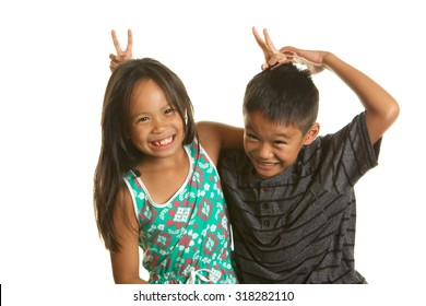 Cute seven year old fraternal twins Playing around on a white background