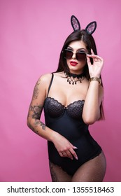 Cute sexy brunette with hooked ears of hare and sunglasses poses on pink background. Studio