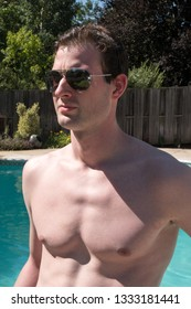 Cute sexy guy with no shirt and hot body standing next to an outdoor swimming pool in the summer sun in aviator sunglasses looking cool and confident. Man with great body posing next to swimming pool.