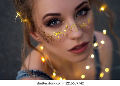 Cute sexy woman in jeans overall outfit with glitter freckles make up and hair buns. Summer evening in the city. Sensual posing in garland golden lights