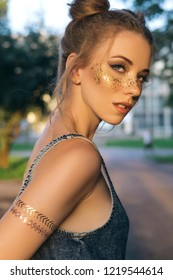 Cute sexy woman in jeans overall outfit with glitter freckles make up and hair buns. Summer evening in the city. Sensual posing