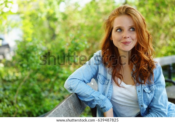 Cute sexy young redhead woman with a quirky smile sitting relaxing on a wooden bench in a park glancing to the side