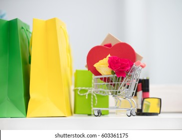 cute shopping bags, make up set, gifts and roses in shopping cart on the wonderful mirror background
