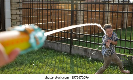 cute short haired schoolboy in checkered shirt enjoys drops flowing from water gun on sunny day close view