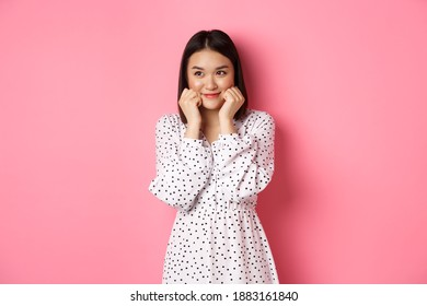 Cute and shy asian girl blushing, touching cheeks and looking left at copy space silly, standing against pink background