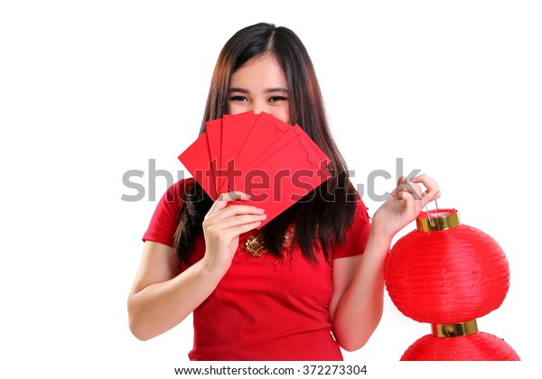 Cute shy Asian teenager in cheongsam dress covering her face with red envelopes while holding a Chinese lantern, isolated on white background