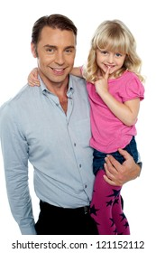 Cute shy little daughter being carried by her handsome father over white background.