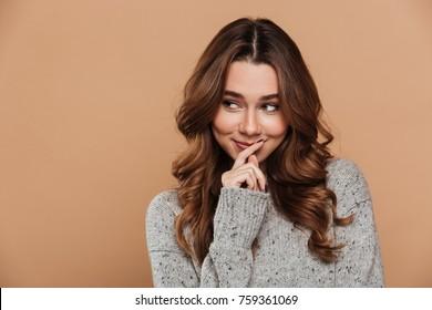 Cute shy woman in woolen jersey looking aside, isolated on beige background