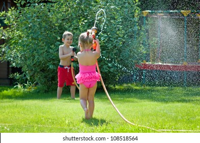 Cute siblings- boy and girl are playing with water on a summer d