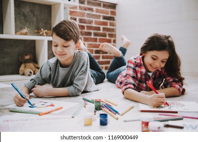 Cute Siblings Drawing Pictures Laying at Floor. Close-up of Caucasian Boy and GIrl Wearing Casual Clothes Rest at White Wooden Floor Using Colorful Pencils, Paper, Stationary. Creative Kids Concept