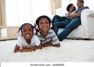 Cute siblings listening music lying on the floor in the living room