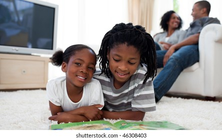 Cute siblings reading lying on the floor in the living room