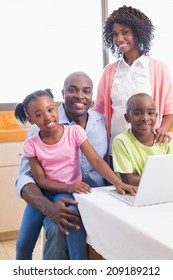 Cute siblings using laptop together with parents at home in the kitchen